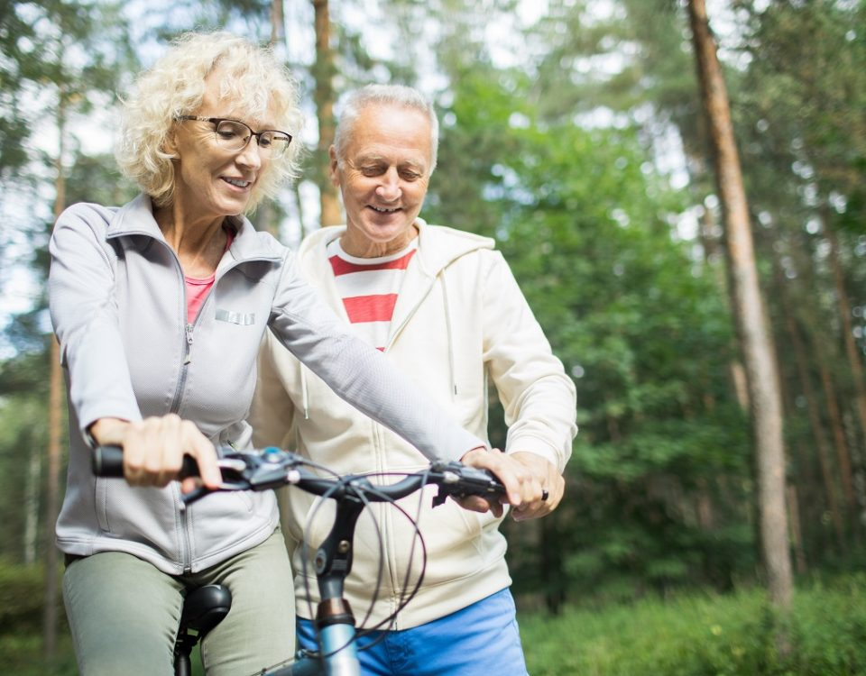 Senior man teaching his wife how to ride bicycle while chilling in park on summer day