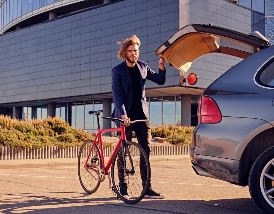Bearded blond male with long hair puts fixed bicycle in the car's trunk.