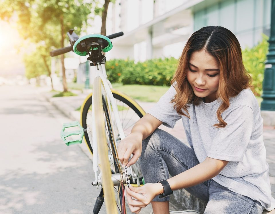 Pretty young Vietnamese woman fixing her bicycle after long ride